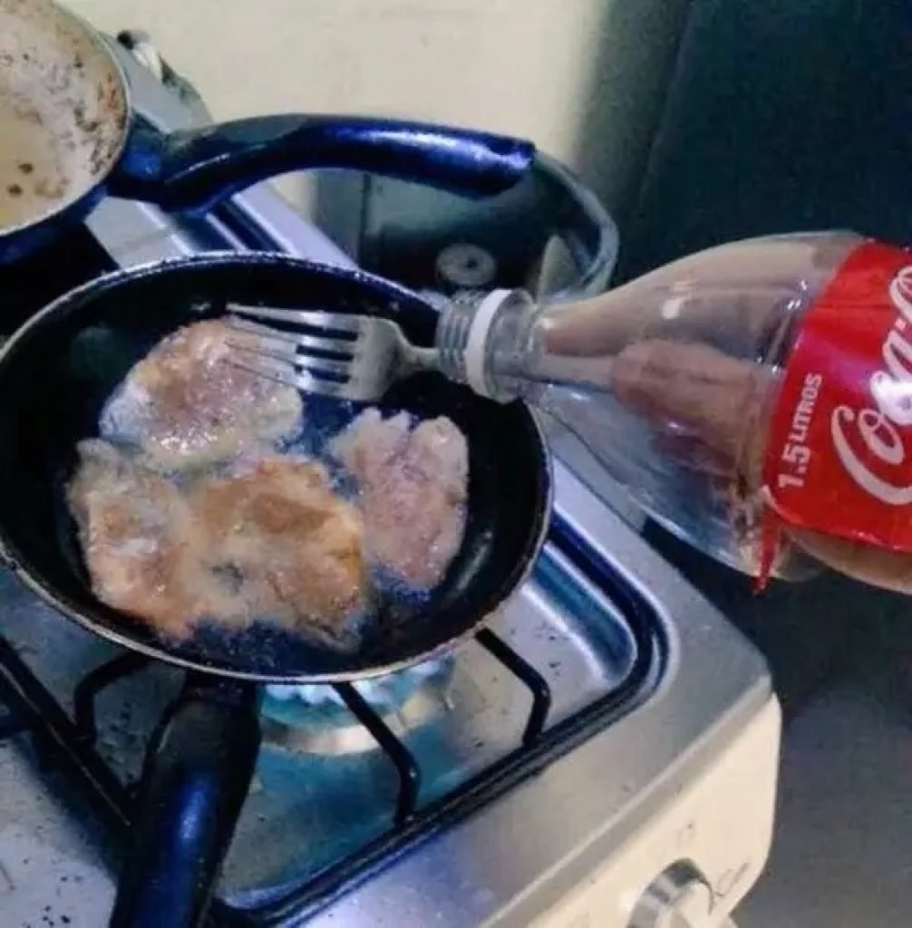 A man frying up chicken with his arm in a coke bottle to protect him from oil splashes