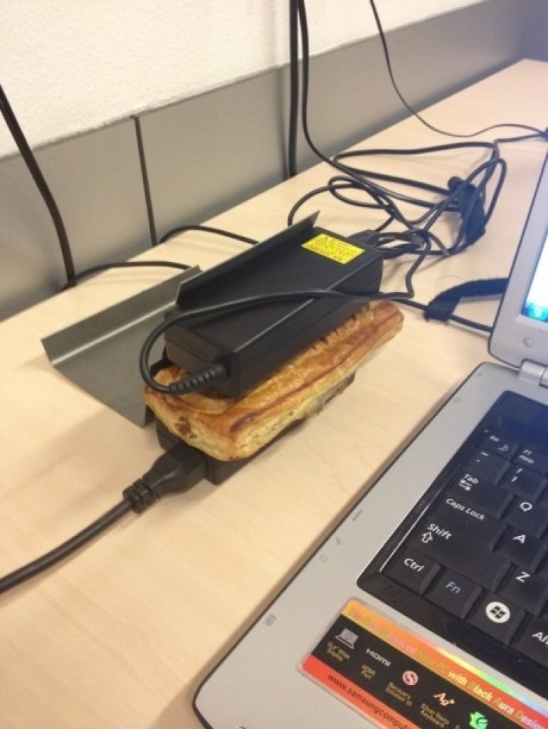 A hot computer charger heating up a panini next to a laptop