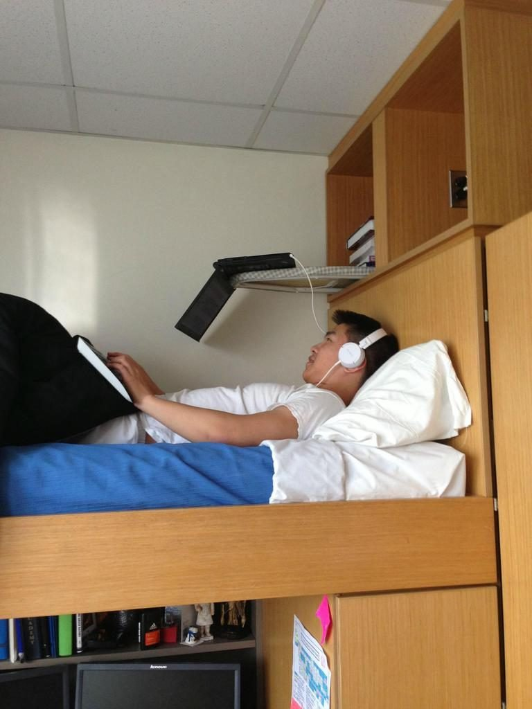 A kid lying in bed and studying at the same time