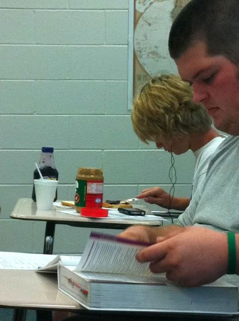 A kid sits in class making a peanut butter and jelly sandwich