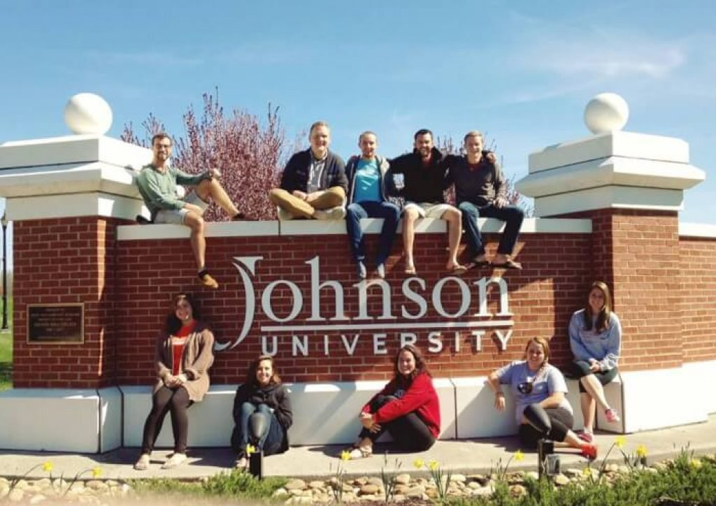 Johnson U students sitting on the front sign