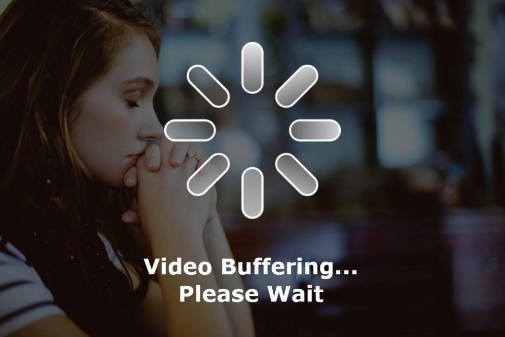 A girl sitting with her head in her hands, frustrated by the buffering on her video