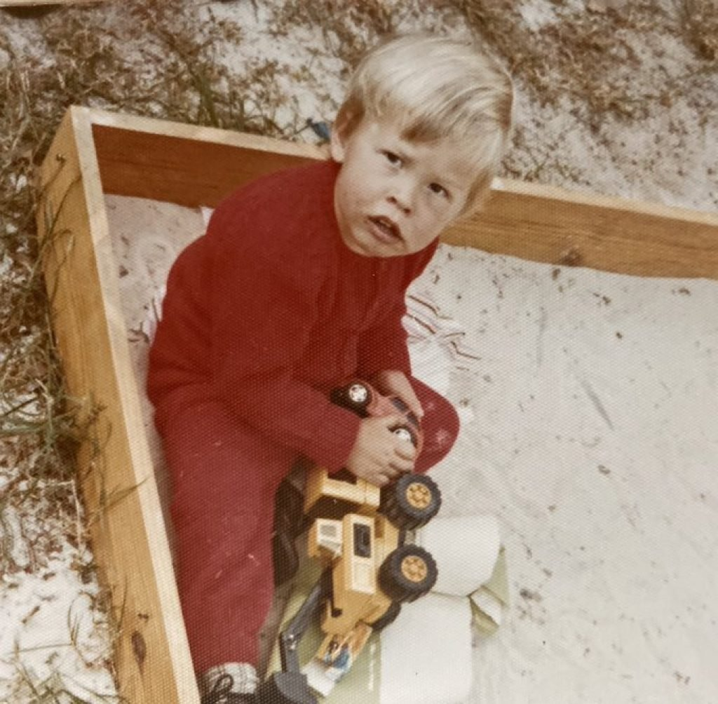 Young Elon playing in the sand box
