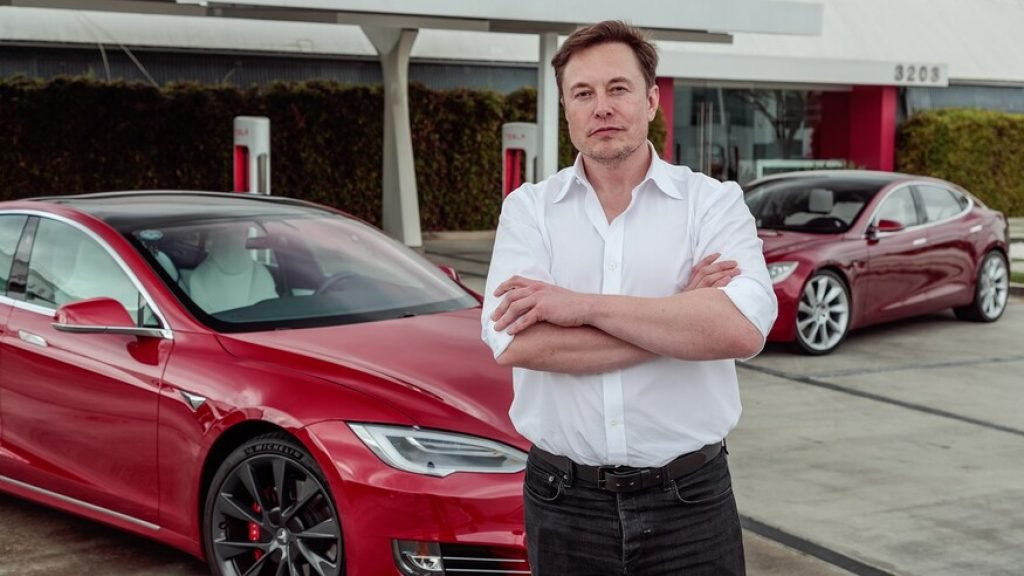 Elon standing in front of a Tesla