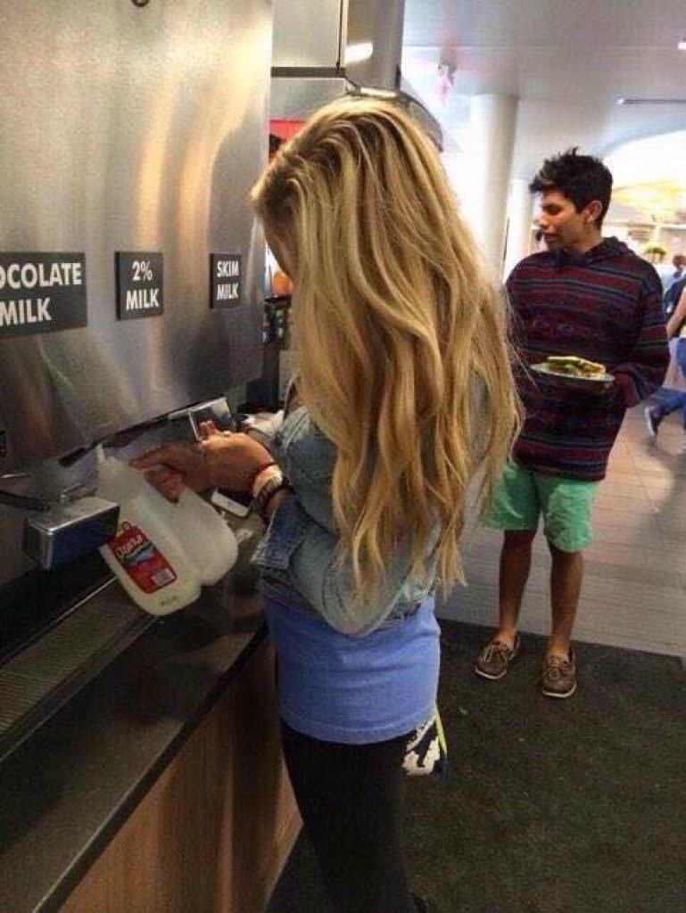 Girl filling up a milk jug in the cafeteria