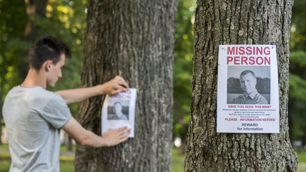 A person putting up missing flyers