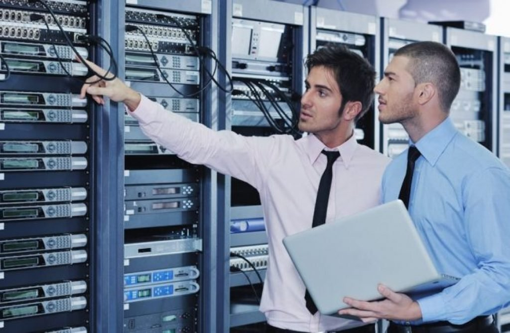 Information technology employees observing a network