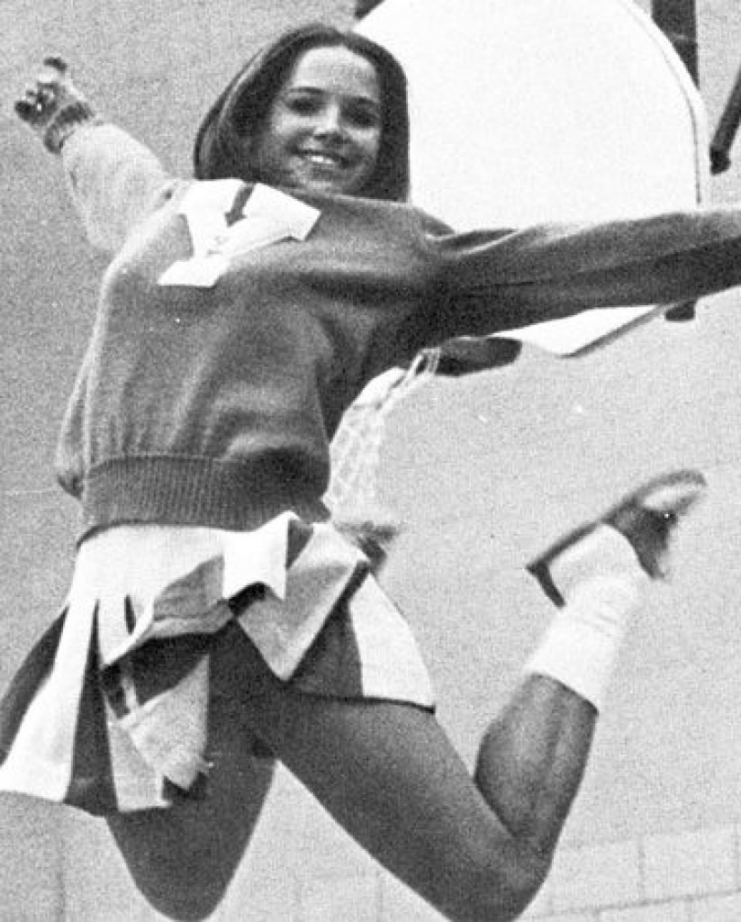 Katie Couric jumping into the air as a cheerleader