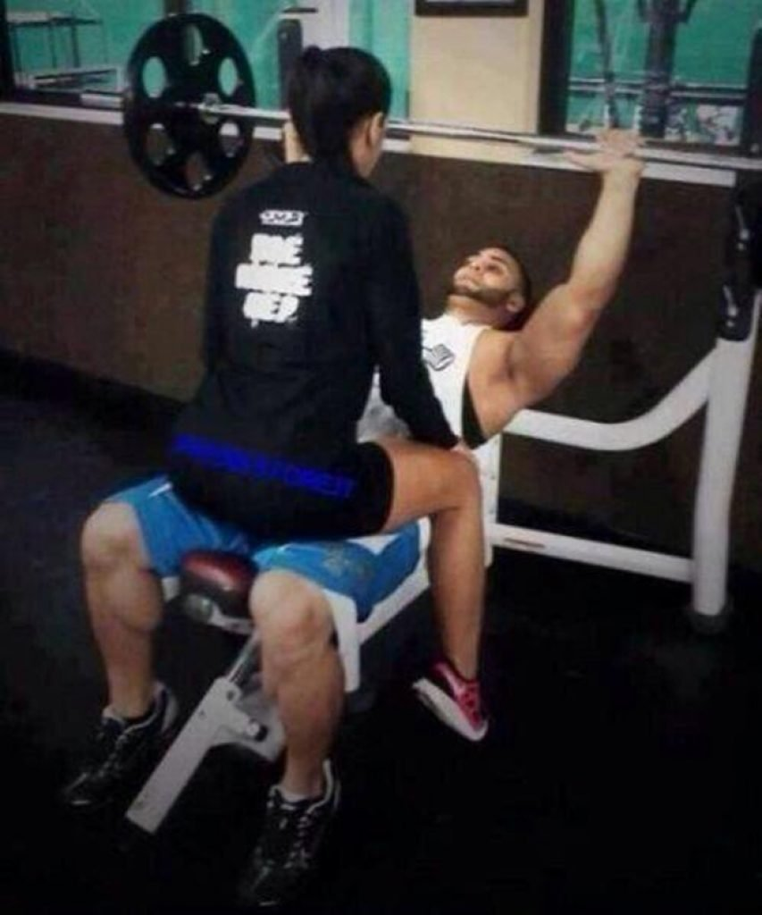 Girl sitting on her boyfriend lifting weights