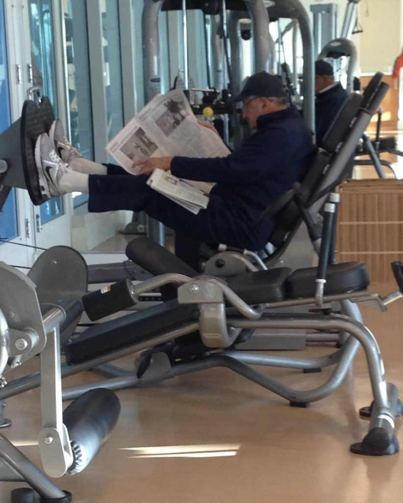Man reading newspaper on weights