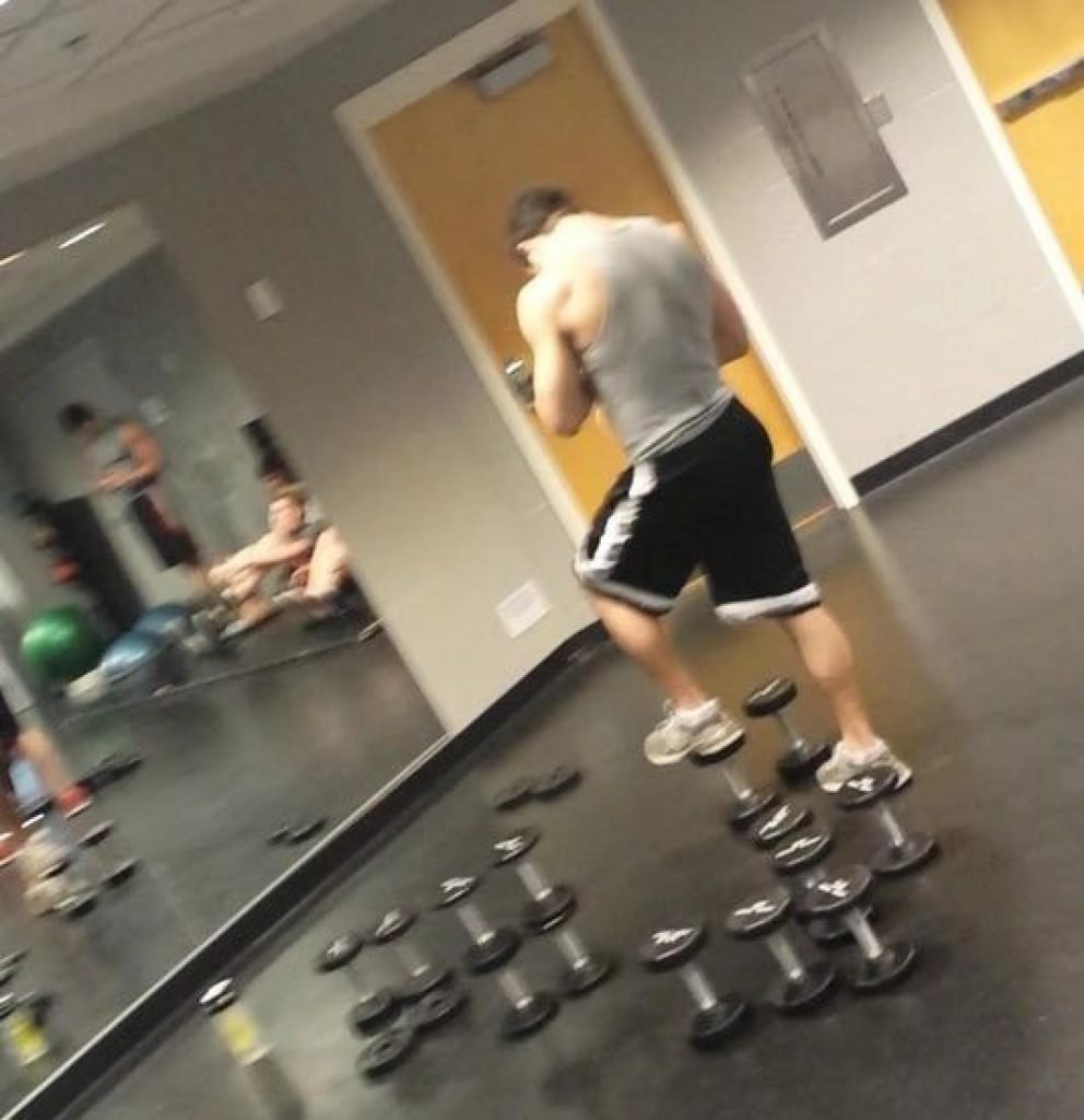 Guy standing on the weights playing on his phone