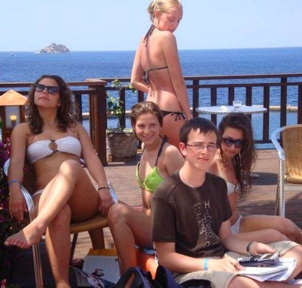 Boy doing math in the middle of girls in bikinis