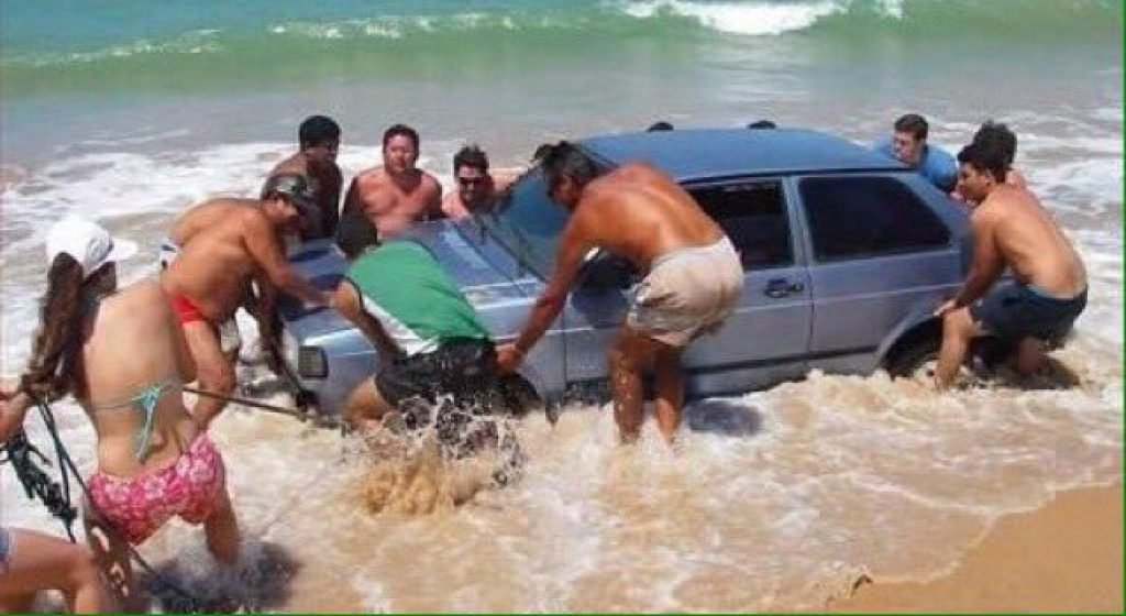 People trying to get their car out of the ocean