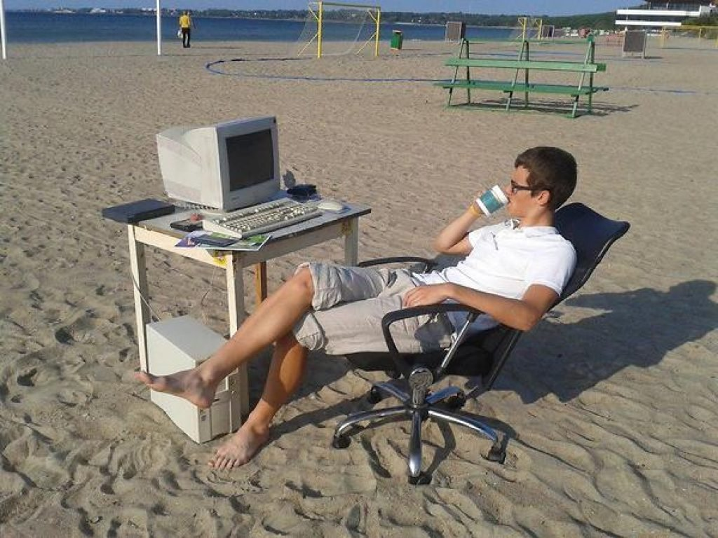 Guy with his computer and desk on the beach