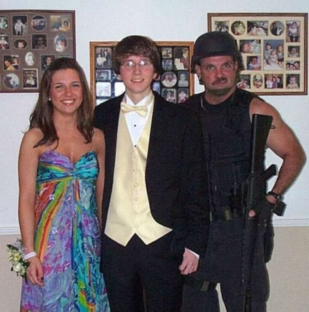 Dad with a gun posing next to his daughter and her prom date